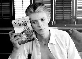 1976 --- David Bowie Holding Buster Keaton Biography --- Image by © Steve Schapiro/Corbis